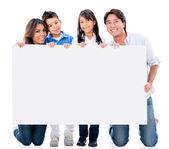 Famille heureuse avec une pancarte — Photo