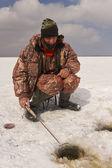 Un homme attrape un poisson de la pêche sur glace. — Photo