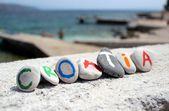 Chorvatsko nápis na kameny s jaderským mořem v pozadí — Stock fotografie