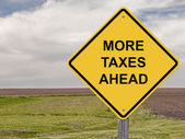 Caution Sign - More Taxes Ahead — Stock Photo