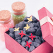 Stock Photo: Black zen stones in a red gift box with red and yellow Ixora flowers