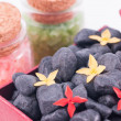 Stock Photo: Black zen stones in a red gift box with red and yellow flowers close up