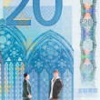 Miniature men chatting with the 20 Euro banknote background — Stock Photo