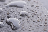 Natural raindrops pattern on wooden table extreme close-up — Stock Photo