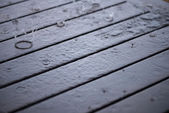 Splashing rain water droplets pattern on wooden table close-up — Stock Photo