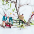 Stock Photo: Miniature workmen cutting and felling trees close up