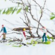 Miniature workmen working together in felling and cutting trees close up — Stock Photo