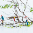 Stock Photo: Miniature workmen working together in felling and cutting trees close up
