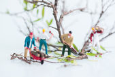 Miniature workmen cutting and felling trees close up — Stock Photo