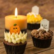 Halloween cupcakes and a burning candle on a rustic wooden table — Stock Photo