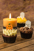 Halloween cupcakes and a burning candle on a rustic wooden table — Stok fotoğraf