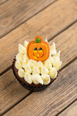 Halloween cupcake with pumpkin cake topper top view — Stock Photo