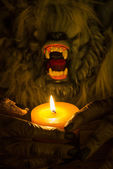 Werewolf head and the hands cradling a candle — Stockfoto