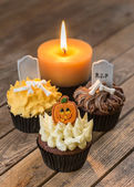 Halloween cupcakes and a candle on old rustic wooden table top view — Stockfoto