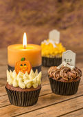 Variation of Halloween cupcakes and candle on a rustic wooden table — Zdjęcie stockowe