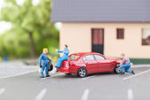 Miniature mechanic changing a punctured tyre — Stock Photo