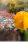 Orange falling into water with natural splashes — Foto Stock