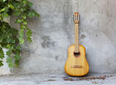 Old classic guitar standing against grungy wall — Stock Photo
