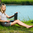 Smiling girl with laptop, beautiful blonde woman sitting under a tree near the calm lake — Stock Photo #12129432