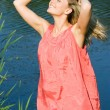 Stok fotoğraf: Beautiful smiling womin red dress in front of water, happy girl summer relaxing