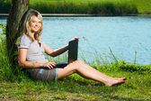 Smiling girl with laptop, beautiful blonde woman sitting under a tree near the calm lake — Stock Photo