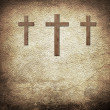 Three wooden crosses on the old brown leather background — Stock Photo