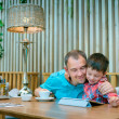 Father and son looking at laptop screen in cafe - Stock Photo