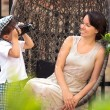 Stock Photo: Cute little boy photographing his mother