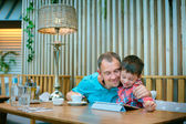 Father and son looking at laptop screen in cafe — Stock Photo