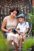Mother and little son with retro camera outdoors — Stock Photo