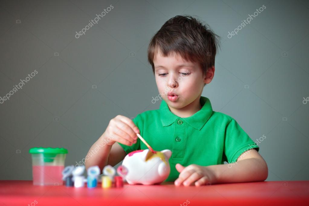 Cute little boy diligently painting his piggy toy indoors — Stock Photo #12456112