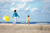 Mother and little son with ballons on the beach — Stock Photo
