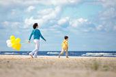 Mutter und sohn mit ballons am strand — Stockfoto