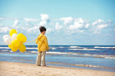 Back view of little boy with ballons on the beach — Stock Photo