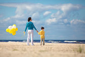 Mother and little son with balloons on the beach — Stock Photo