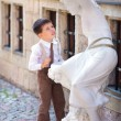 Cute little boy looking at white statue — Stock Photo #13591440