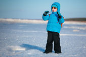 Cute little boy having fun on winter beach — Stock Photo