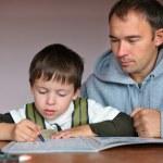 padre ayudando a hijo haciendo los deberes — Foto de Stock