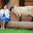 Young woman and her little son feeding a sheep — Stock Photo