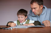 Father helping son doing homework — Stock Photo