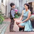 Little son giving a flower to mother - Stockfoto