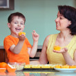 Royalty-Free Stock Photo: Smiling young mother and son baking muffins