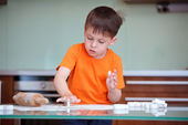 Cute kid helping at kitchen with baking cookies — Stock Photo