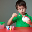 Cute little boy painting his piggy toy — Stock Photo