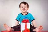 Glada barnet pojke med en presentförpackning — Stockfoto