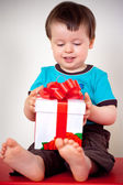 Happy toddler boy opening a gift box — Stock fotografie