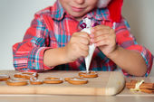 Close up of kid decorating the gingerbread cookies — Stock Photo