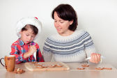 Mother and son decorating the gingerbread cookies — Stock Photo