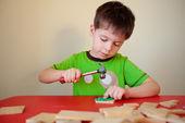 使用锤子和钉子的可爱男孩 — 图库照片