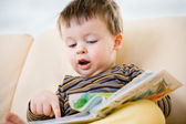 Cute little boy reading book on sofa — Stock Photo